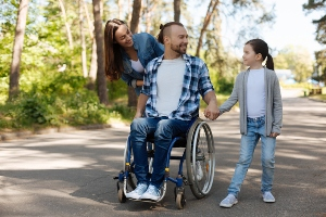 Family with man using wheelchair and young child explore a park