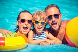 Happy family on vacation in swimming pool wearing sunglasses