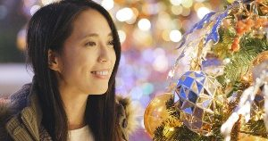 Woman gazing at Christmas tree at theme park holiday celebration