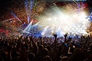 Crowd at an Orlando concert with hands in the air, confetti, and bright lights