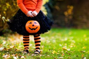Child in orange and black halloween costume, holding jack-o-lantern candy jar