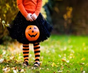 Young girl holding jack-o-lantern candy basket