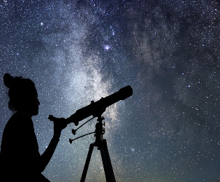Woman using telescope to view stars and constellations