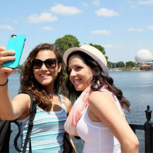 Two females taking picture in front of water