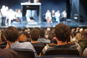 Group of people sitting in theater watching a play onstage